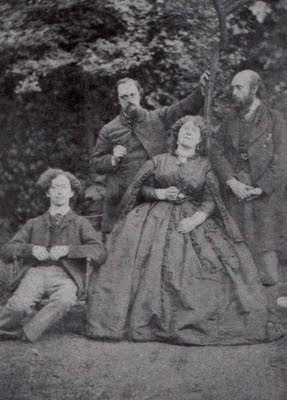 Algernon Swinburne, Dante Gabriel Rossetti, Fanny Cornforth, and William Michael Rossetti posing in a sort of mock family portrait in the garden of 16 Cheyne Walk.
